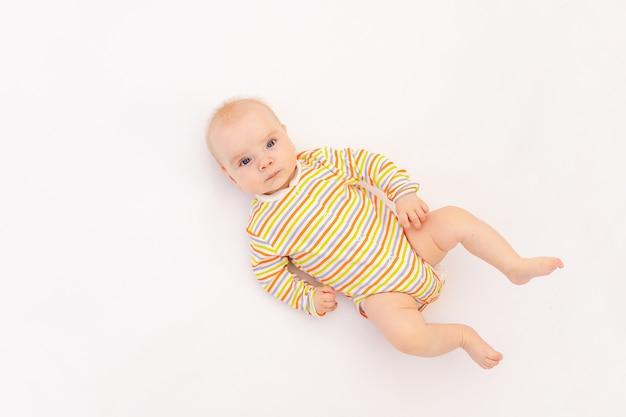Glimlachend babymeisje 6 maanden oud liggend in een lichte romper ,, bovenaanzicht.