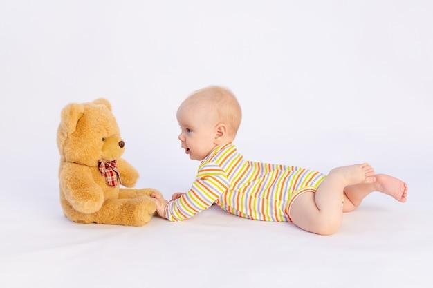 Glimlachend babymeisje 6 maanden oud ligt op een witte geïsoleerde achtergrond in een lichte romper voor een zachte teddybeer, ruimte voor tekst