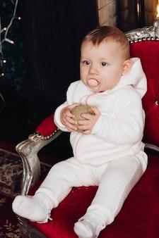 Glimlachend babymeisje die onder 1 éénjarige kerstboom in ruimte verfraaien. camera kijken. viering. vakantie seizoen.