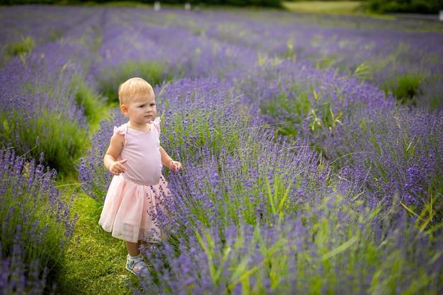 Glimlachend babymeisje in roze jurk in een lavendelveld tsjechië