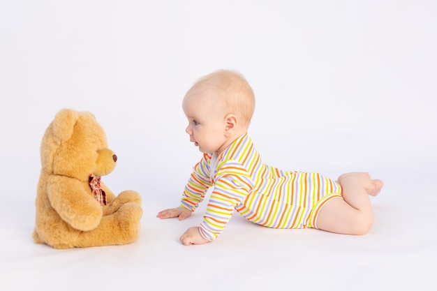 Glimlachend babymeisje ligt op wit geïsoleerd in een lichte romper voor een zachte teddybeer