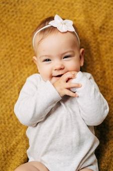 Glimlachend babymeisje met een bloem op haar hoofd in een witte blouse ligt