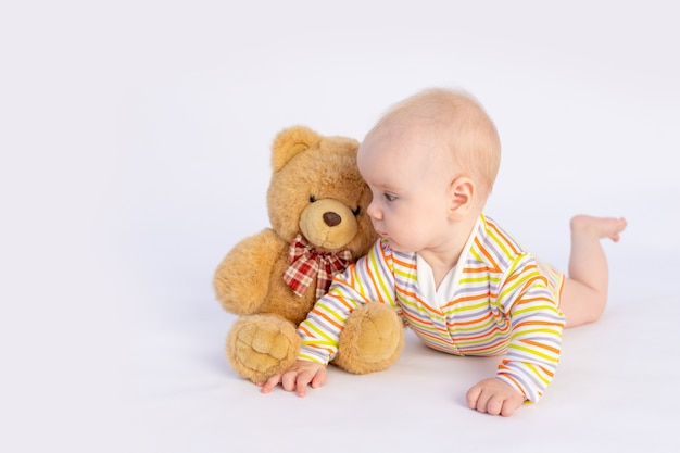 Glimlachend babymeisje van 6 maanden oud ligt in een lichte bodysuit met een zachte teddybeer,