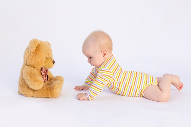 Glimlachend babymeisje van 6 maanden oud ligt in een lichte romper voor een zachte teddybeer,