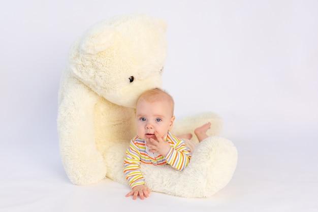 Glimlachend babymeisje van 6 maanden oud ligt met een grote zachte teddybeer,