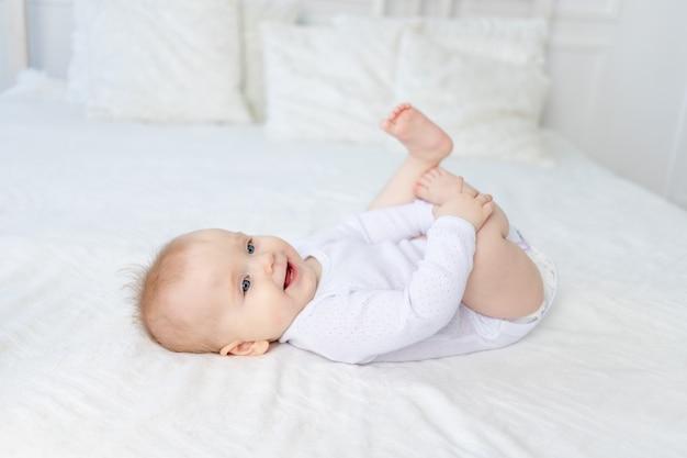 Glimlachend babymeisje van zes maanden oud speelt met haar benen op haar rug op een wit katoenen bed in de slaapkamer van het huis en lacht