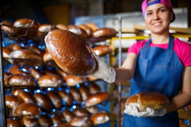 Glimlachend bakkersmeisje die in schort brood houden en camera bekijken. de jonge vrouw is een chef-kok die vers baksel houdt. een gelukkig meisje met een europese uitstraling lacht naar de bakkerij.