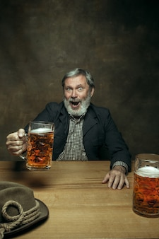 Glimlachend bebaarde man bier drinken in pub