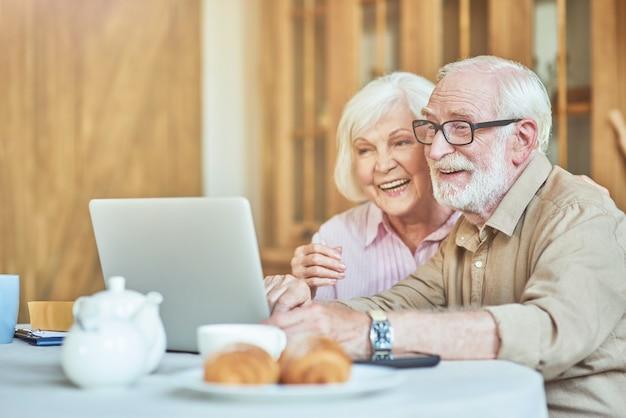 Glimlachend bejaarde echtpaar kijken naar grappige video op computer