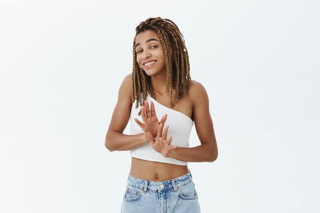 Glimlachend beleefd afrikaans-amerikaans meisje dat aanbod keurig afwijst, handen schudt in ontkenning of weigering