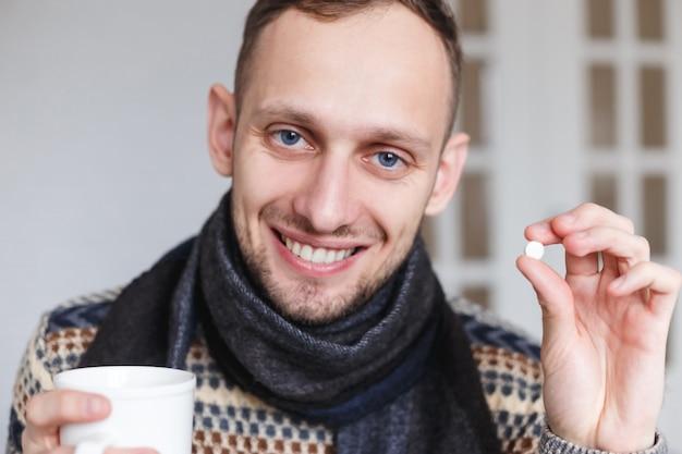 Glimlachend betrapt toont een koude man pillen voor gezondheid alvorens te nemen