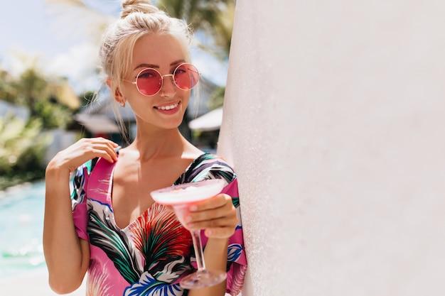 Glimlachend bevallig meisje met blond haar poseren met cocktail.