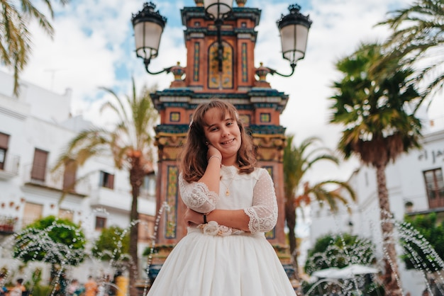 Glimlachend blanke meisje gekleed in communie jurk leunend op haar arm naast een oude fontein