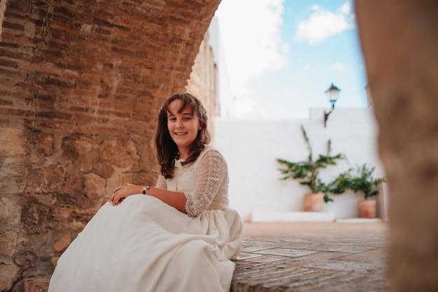 Glimlachend blanke meisje met bruin haar zittend op een stenen trap, gekleed in communie