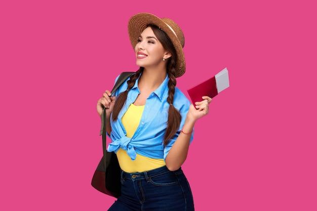 Glimlachend blanke vrouw student met paspoort en vliegtickets. meisje in vrijetijdskleding en strohoed. vrouwelijke reiziger op roze geïsoleerde achtergrond.