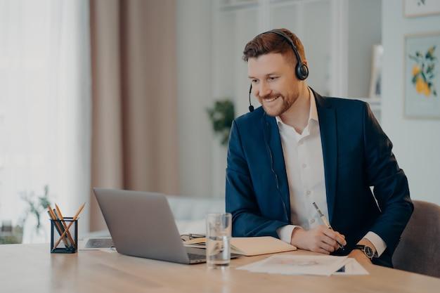 Glimlachend blij succesvolle zakenman praktijken online conferentie heeft afstandsvergadering met collega's draagt headset gericht op laptopcomputer draagt formele kleding. freelance werkconcept.