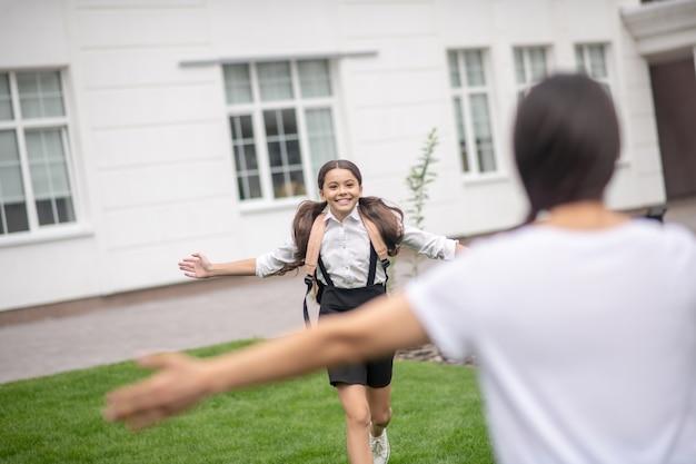 Glimlachend blije langharige schoolmeisje met rugzak loopt om moeder te ontmoeten met uitgestrekte armen