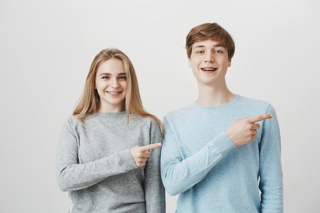 Glimlachend blond kerel en meisje met steunen die manier tonen, wijzend vingers juist