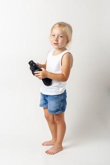 Glimlachend blond kind met een verrekijker op een lichte achtergrond in de studio.