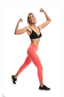 Glimlachend blond meisje in uniform sport toont spieren. volledige hoogte. actieve levensstijl en gezondheid