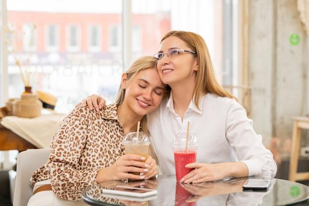 Glimlachend blond meisje met chocoladecocktail die haar hoofd op moederschouder houdt terwijl beide na het winkelen aan de tafel in het café zitten
