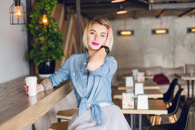 Glimlachend blond meisje zit in een coffeeshop koffie drinken en haar haren aan te raken. in het café staan houten stoelen en tafels