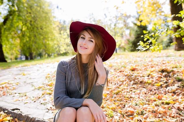 Glimlachend blond model in rode hoed poseren in het bos, trendy gebreide jurk dragen