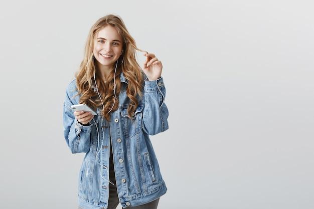 Glimlachend blond mooi meisje met behulp van mobiele telefoon, muziek in koptelefoon luisteren