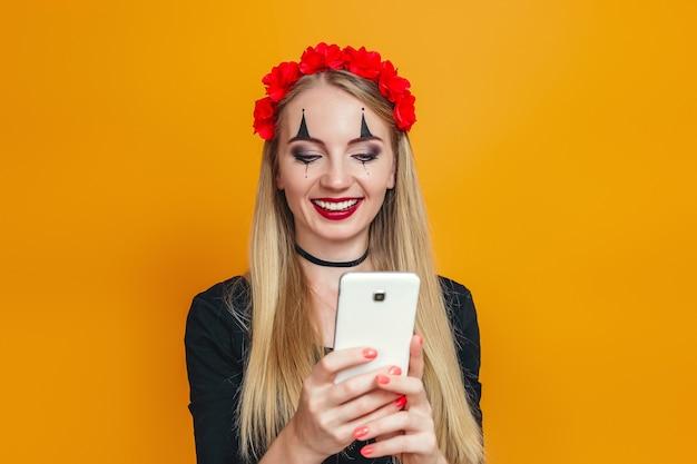 Glimlachend blondemeisje in zwarte kleding en halloween-kostuum die een mobiele telefoon houden die op oranje wordt geïsoleerd