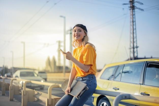 Glimlachend blondemeisje met een skateboard in de stad