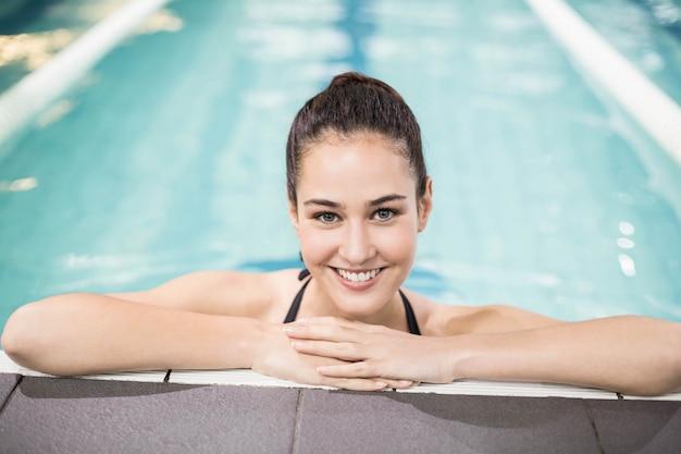 Glimlachend brunette die op poolside in zwembad leunen