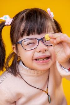 Glimlachend buitengewoon jong meisje met een psychische stoornis die tarwevlok in haar handen toont