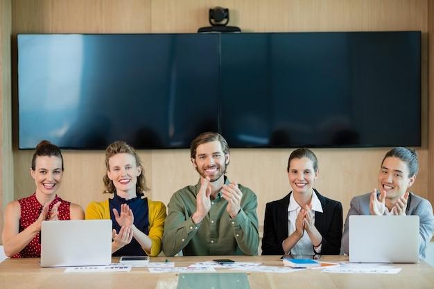 Glimlachend business team applaudisseren tijdens de bijeenkomst in de vergaderruimte