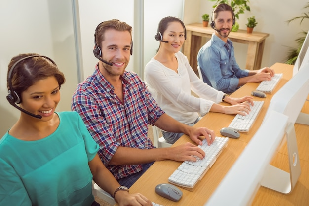 Glimlachend call centreteam die de camera bekijken