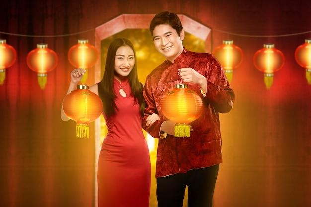 Glimlachend chinees paar met cheongsamkleding die rode lantaarns houden