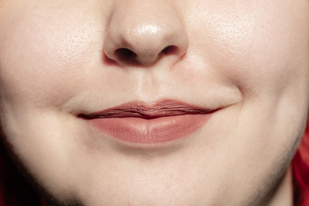Glimlachend. close-up van vrouwelijke mond met natuurlijke lippensamenstelling en goed bewaarde wangenhuid