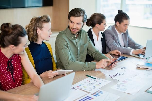 Glimlachend commercieel team dat met elkaar in vergaderruimte in wisselwerking staat