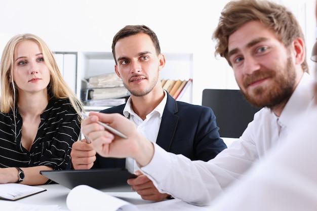 Glimlachend commercieel team in kostuum op werkplaats