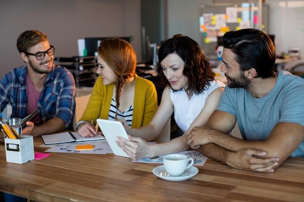 Glimlachend creatief business team bespreken over digitale tablet aan balie in kantoor