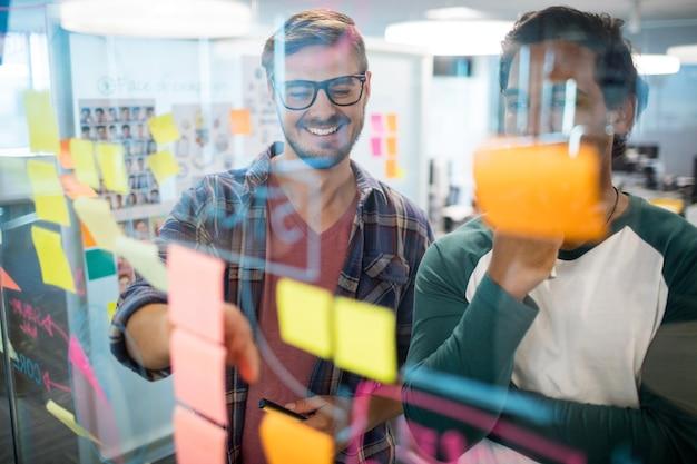 Glimlachend creatief commercieel team dat plaknotities in bureau leest