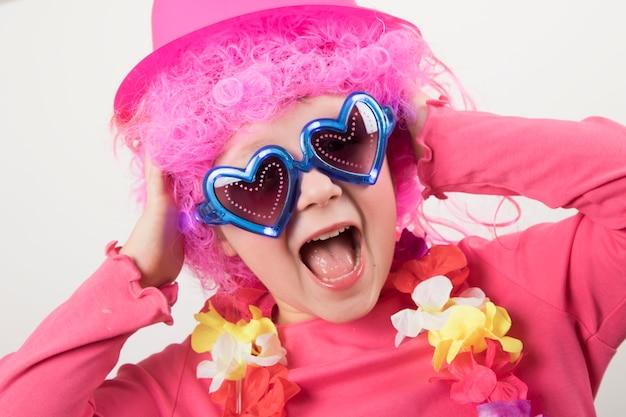Glimlachend die meisje in clownpruik op witte achtergrond wordt geïsoleerd