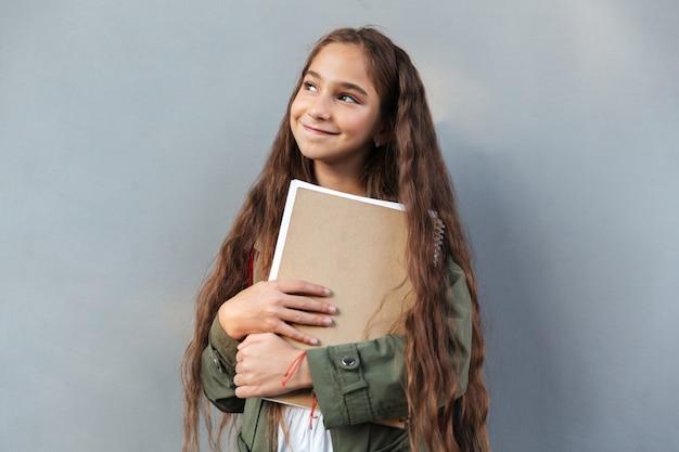 Glimlachend donkerbruin schoolmeisje met lang haar gekleed in warme kleren