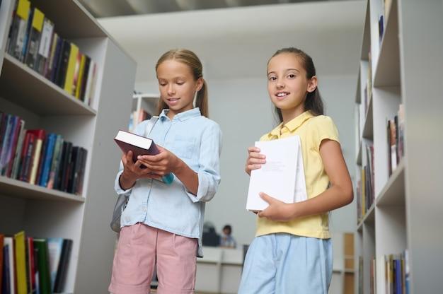 Glimlachend donkerharig meisje met leermateriaal en haar klasgenoot met een boek dat tussen boekenplanken staat