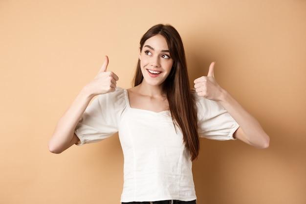Glimlachend dromerig meisje kijkt naar de linkerbovenhoek en duimen opdagen bij promo, product aanbevelen, banner prijzen, staande op beige achtergrond.