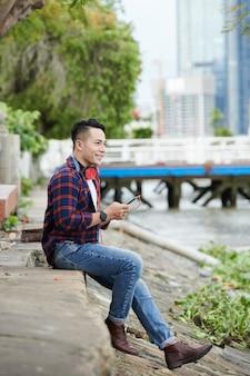 Glimlachend dromerige jonge aziatische man met rode koptelefoon om de nek zittend op de grond in de buurt van de rivier en het nummer kiezen op smartphone