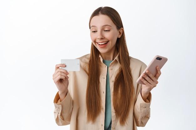 Glimlachend duizendjarig meisje met smartphone, tevreden kijkend naar creditcard, betalen op internet, online bestellen, winkelen met applicatie op telefoon, over witte muur staan