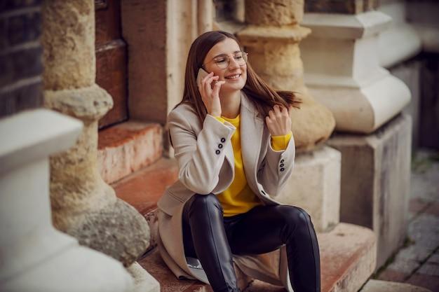 Glimlachend duizendjarige meisje, zittend op de ingang van een oud gebouw en chatten met vriend aan de telefoon.