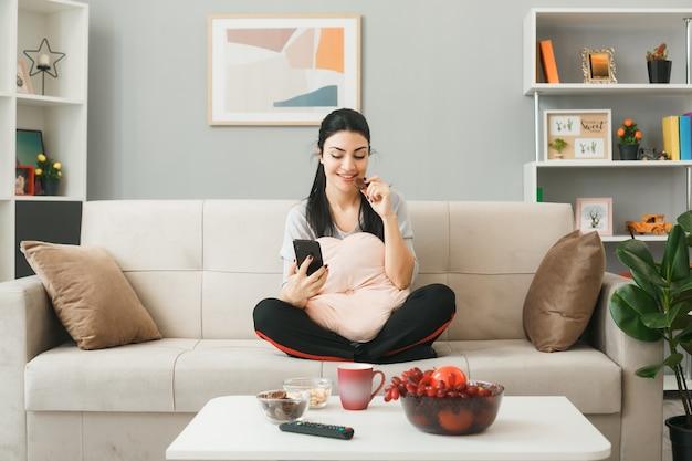 Glimlachend eet koekjes jong meisje met kussen zittend op de bank achter de salontafel, vasthoudend en kijkend naar de telefoon in de woonkamer
