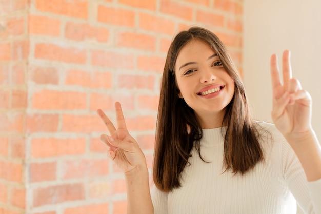Glimlachend en er gelukkig, vriendelijk en tevreden uitziend, gebarend naar overwinning of vrede met beide handen