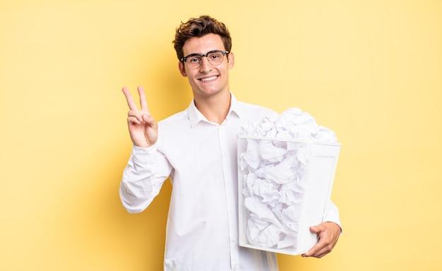 Glimlachend en er gelukkig, zorgeloos en positief uitziend, gebarend naar overwinning of vrede met één hand. prullenbak papier concept